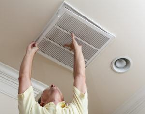 Man reaching up to open filter holder for air conditioning filter in ceiling